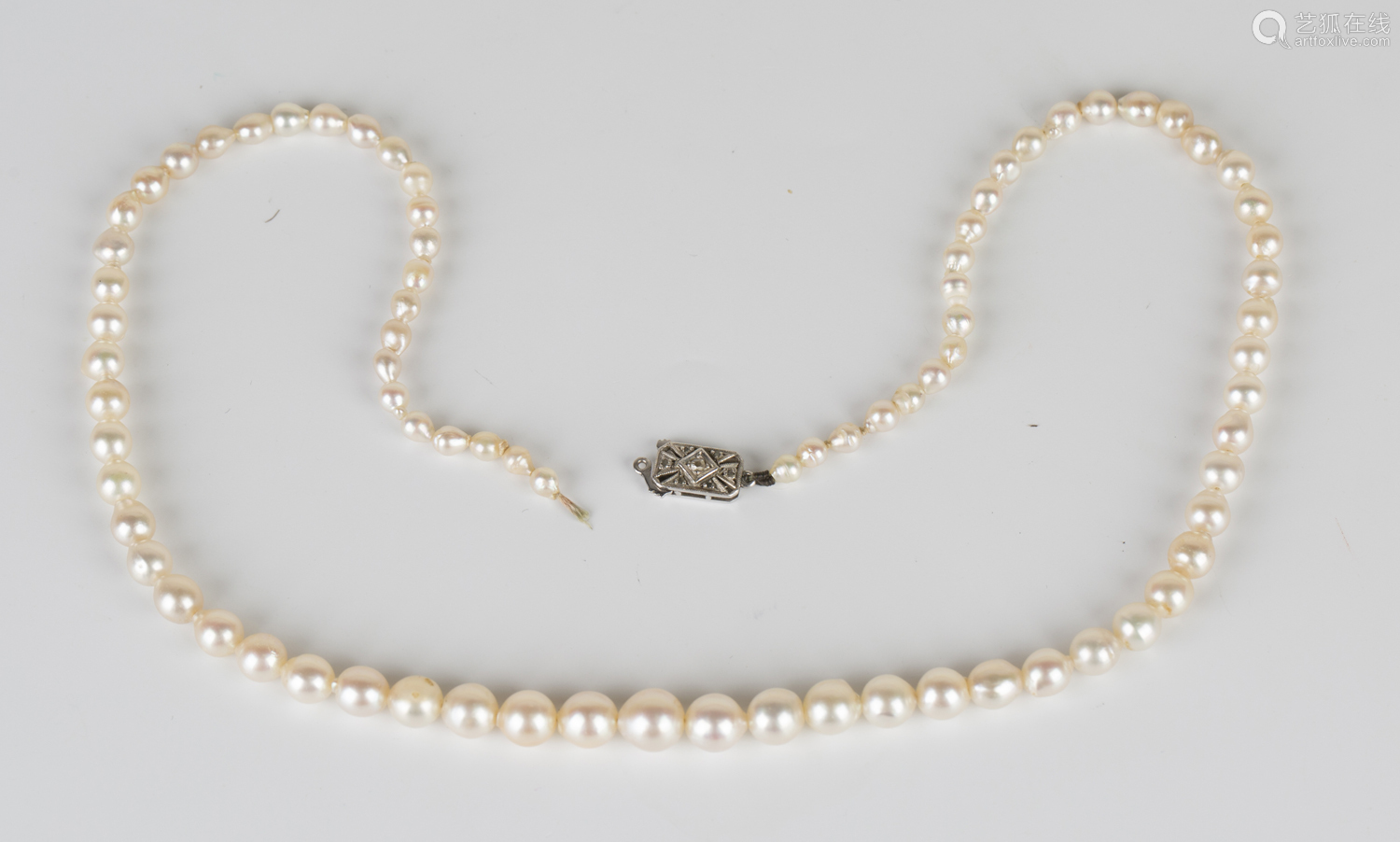 A single row necklace of graduated cultured pearls on a diamond set rectangular clasp, length
