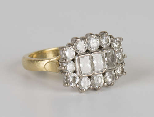 An 18ct gold and diamond ring, mounted with three rectangular cut diamonds within a surround of