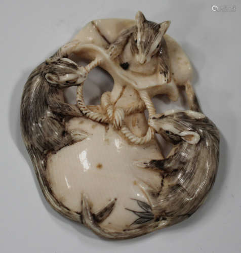 A Japanese ivory netsuke, Meiji/Taisho period, carved, pierced and stained with three rats upon a