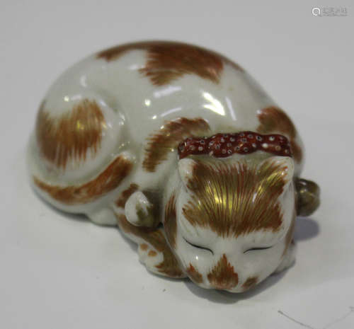 A Japanese Kutani porcelain netsuke, Meiji/Taisho period, modelled as a sleeping cat with iron red