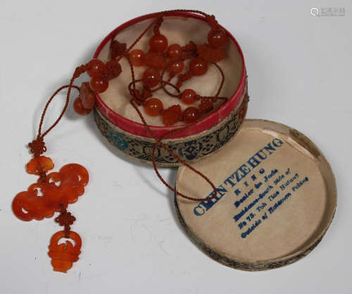 A Chinese carnelian pendant and bead necklace, 20th century, the pendant of carved and pierced