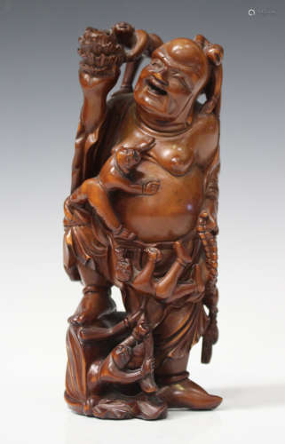 A Chinese carved boxwood figure group of a smiling Buddha, early 20th century, modelled standing and