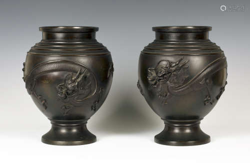 A pair of Japanese brown patinated bronze vases, Meiji period, each ovoid body cast in relief with a