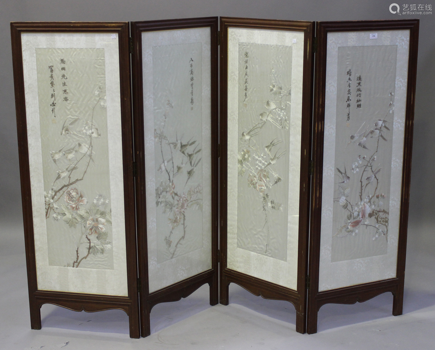 A Chinese hardwood and silk embroidered four-fold screen, late Qing dynasty, each glazed panel