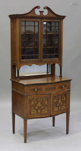 An Edwardian mahogany and foliate inlaid display cabinet, the swan neck pediment above a pair of