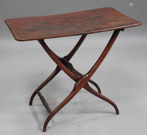 A mid-19th century mahogany coaching table, the curved rectangular top above a folding base,