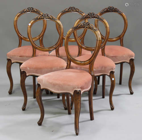 A set of six Victorian walnut spoon back dining chairs with carved decoration, the overstuffed seats