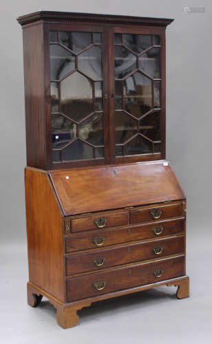 A George III mahogany bureau bookcase, the dentil moulded pediment above a pair of astragal glazed