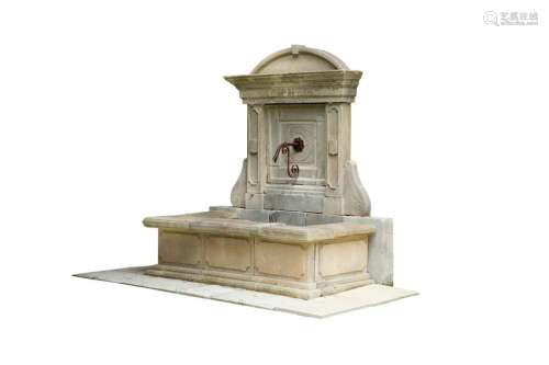 Fontaine murale en pierre. Le fronton présente une…