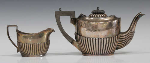 An Edwardian silver bachelor's teapot with half-reeded decoration and a matching milk jug,
