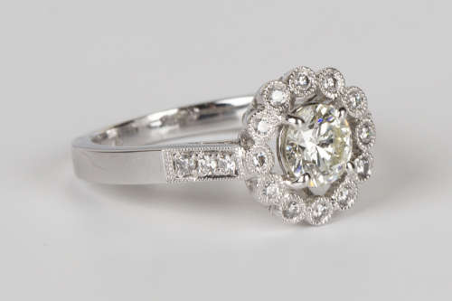 A white gold and diamond ring, claw set with the principal circular cut diamond within an open
