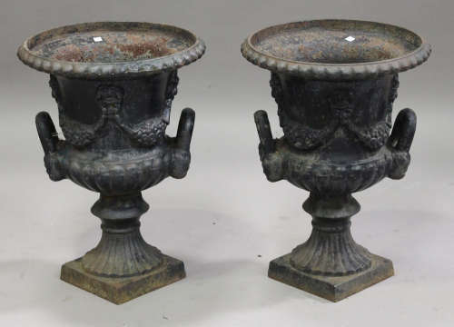 A pair of 20th century cast iron garden urns of half-reeded campana form, the bodies with floral