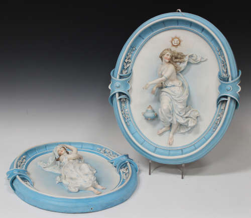 A large pair of French bisque porcelain oval wall plaques, circa 1900, each moulded in high relief