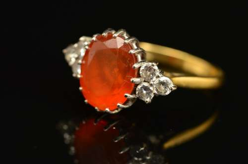 A LATE 20TH CENTURY FIRE OPAL DRESS RING, centring on an oval mixed cut fire opal, measuring