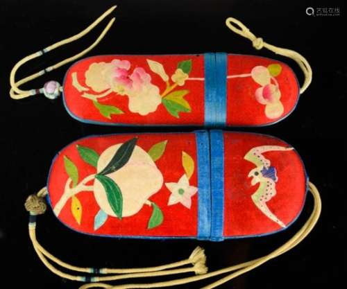 Two Chinese silk applique spectacle cases, circa 1930, both with red silk ground and blue borders,