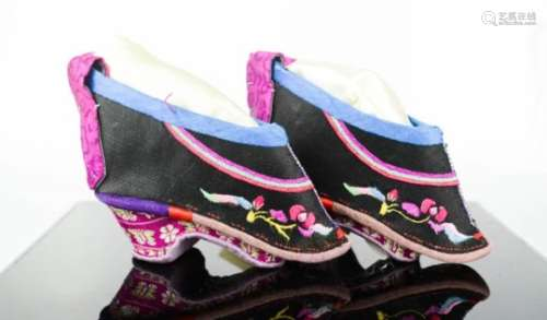 A pair of Chinese lotus shoes circa 1910, the black silk embroidered with flowers, 10cm sole length.