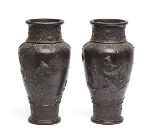 A set of two Japanese bronze vases both decorated with a relief of birds, lotus flowers and trees.