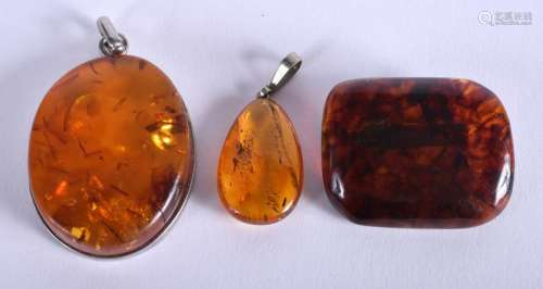 THREE AMBER PENDANTS. (3)