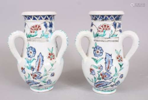 A PAIR OF IZNIK STYLE POTTERY THREE HANDLED VASES, 25cm high.