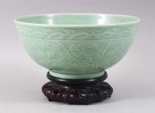 A GOOD CHINESE CELADON CARVED BOWL & HARDWOOD STAND, the bowl carved with formal scrolling lotus and