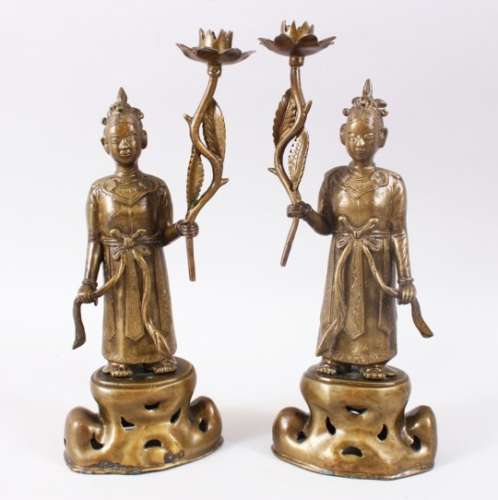 A GOOD PAIR OF 20TH CENTURY CHINESE BRONZE CANDLE STICKS, in the form of figures holding flowers,
