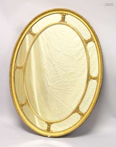 A LATE 19TH CENTURY ADAM REVIVAL GILT FRAMED OVAL WALL MIRROR, with gadroon carved frame. 3ft 8.5ins