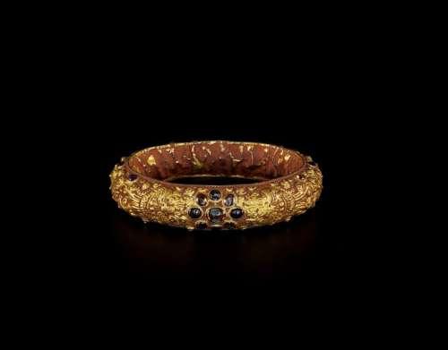 A CHAM REPOUSSÉ GOLD BRACELET WITH A GEMSTONE FLOW…