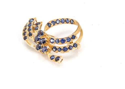 A sapphire and gold scroll brooch, the circular and oval bale sapphires in scroll design all in