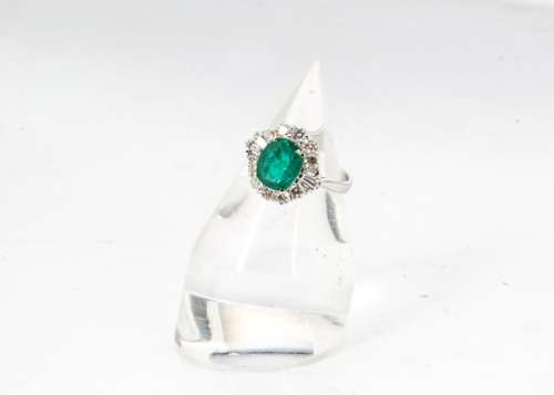 An emerald and diamond Art Deco style dress ring, central oval cut emerald in four claw setting