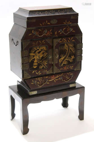 Oriental small cabinet decorated in a chinoiserie aesthetic style, seated on plain wooden stand,