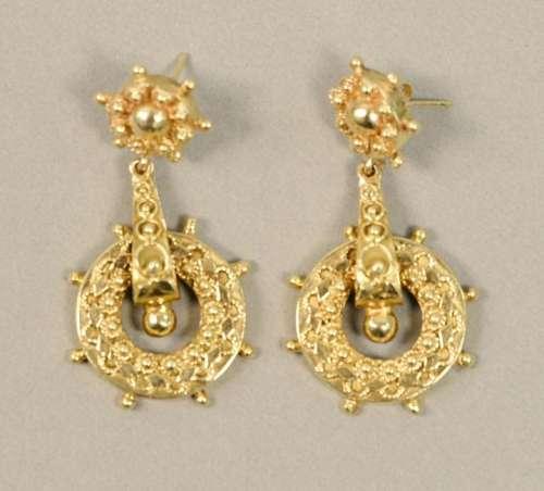 Pair of 14K gold pierced earrings with ships wheel