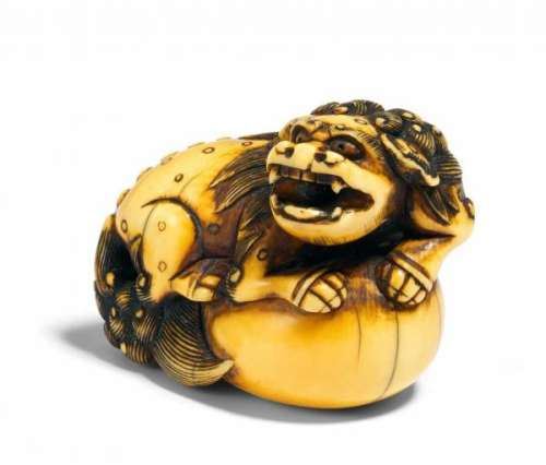 NETSUKE OF A SHISHI LION ON A BIG BALL. Japan. 18th c. Ivory, the engraving stained [...]