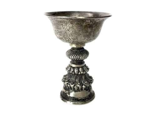 A CHINESE/TIBETAN WHITE METAL LIBATION CUP