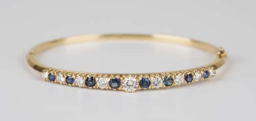 An 18ct gold, sapphire and diamond oval hinged bangle, the front claw set with the principal