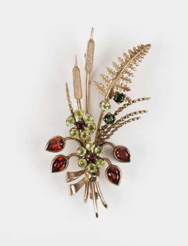 A 9ct gold, garnet and peridot brooch, designed as a spray with two floral clusters, bulrushes and