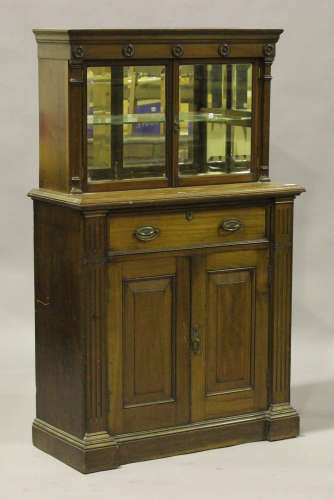 A Victorian mahogany side cabinet, the moulded pediment above a pair of glazed doors revealing a