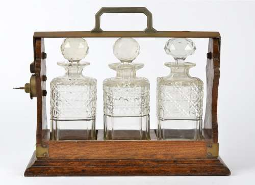 An oak framed tantalus, containing three cut glass decanters, with key