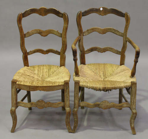 A set of eight 19th century French limed beech ladder back dining chairs, comprising two carvers and
