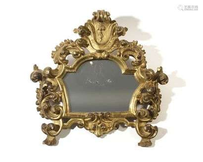 Gilded wooden mirror with openwork decoration of foliage and staples, (glass probably replaced).  18th century.  H : 58 cm, W : 60 cm