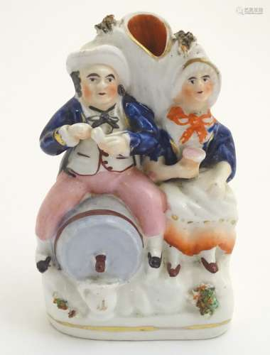 A Victorian Staffordshire pottery flatback spill vase depicting a man and a woman,