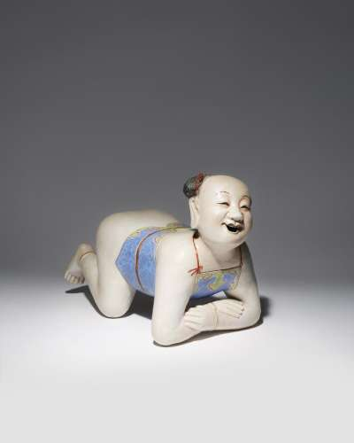 A LARGE CHINESE FAMILLE ROSE PILLOW MODELLED AS A BOY QING DYNASTY OR LATER The child depicted