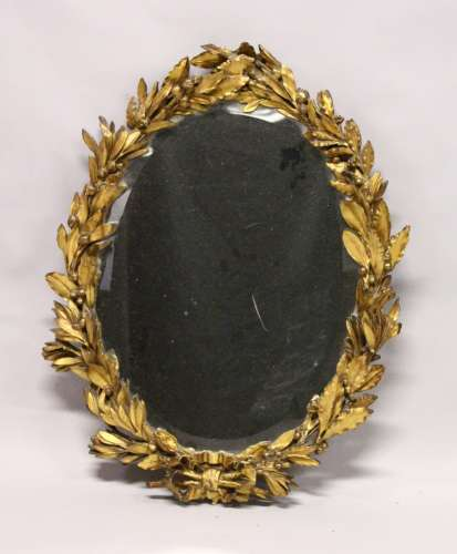 AN 18TH / 19TH CENTURY GILT FRAMED OVAL MIRROR, with well carved leaf and berry frame and ribbon and