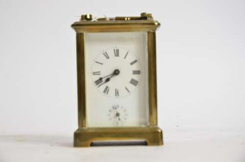 A brass carriage timepiece, the central enamel dial with Roman numerals and lower Arabic dial,