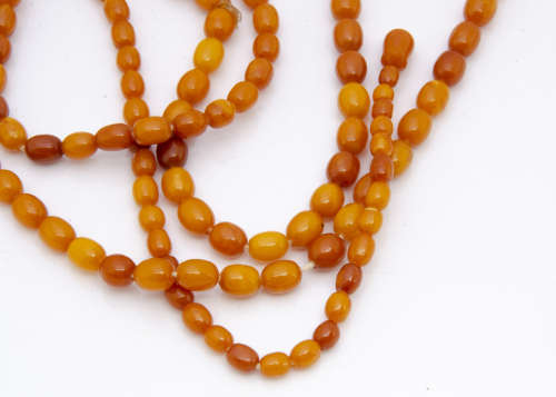 An opera len*** string of uniform oval butterscotch amber beads, 88cm long together, 9.5mm diameter,