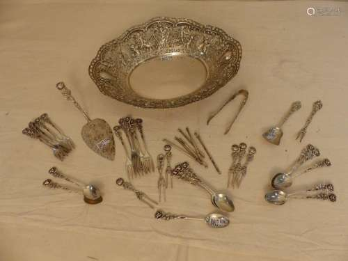 A basket and a set of small forks, spoons, etc... …