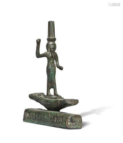 An Egyptian bronze figure of Onuris standing on a boat