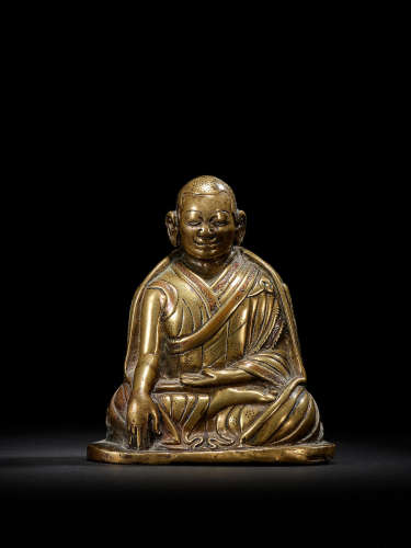 A COPPER INLAID BRASS FIGURE OF A KAGYU HIERARCH CENTRAL TIBET, CIRCA 13TH CENTURY