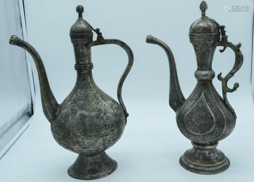Two Middle Eastern metal embossed Ewers