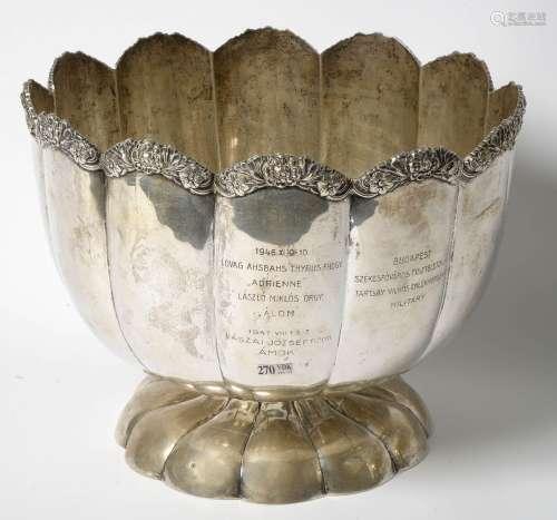 Important seau à champagne godronné à bordure florale en argent 800/1000ème aux poinçons hongrois, poinçon d'orfèvre non identifié. Portant plusieurs dédicaces datées, une de 1904 et les autres 1946 et 1947. H.:+/-28,5cm. Poids total.:+/-2600grs.