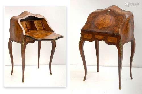 小巧的路易十五风格的女式书桌,单板木,内外镶嵌。花卉镶嵌,外墙装饰有国徽,内有塔楼。由叶子打开的六个抽屉,并在皮带上提供三个抽屉。镀金铜饰。奥地利的工作。1900年左右。尺寸:+/-63x100x41cm。